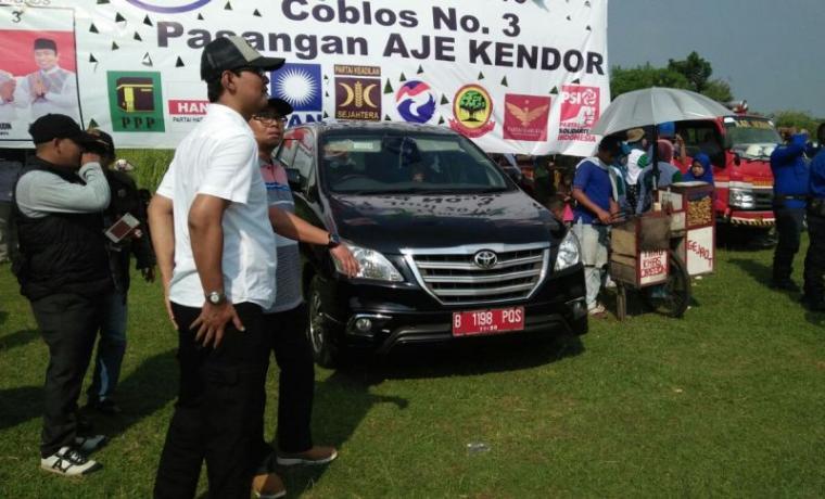 Mobil dinas dengan nomor polisi B 1198 PQS yang terparkir di acara rapat umum pasangan calon Wali Kota dan Wakil Wali Kota Serang Syafrudin-Subadri Usuludin, di Lapangan Boru, Kecamatan Curug, Kota Serang. (Foto: TitikNOL)