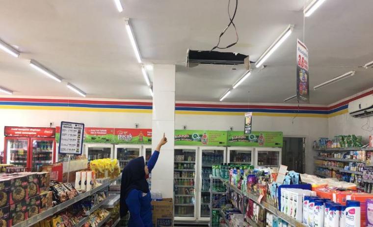 Pegawai Indomaret saat menunjukan plafon yang dijebol oleh kawanan pencuri. (Foto: TitikNOL)