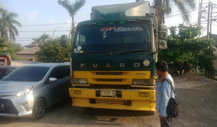 Seorang warga berdiri di depan truk tronton nopol N 8783 UJ muatan miras, yang diamankan di Mapolres Cilegon. (Foto: TitikNOL)