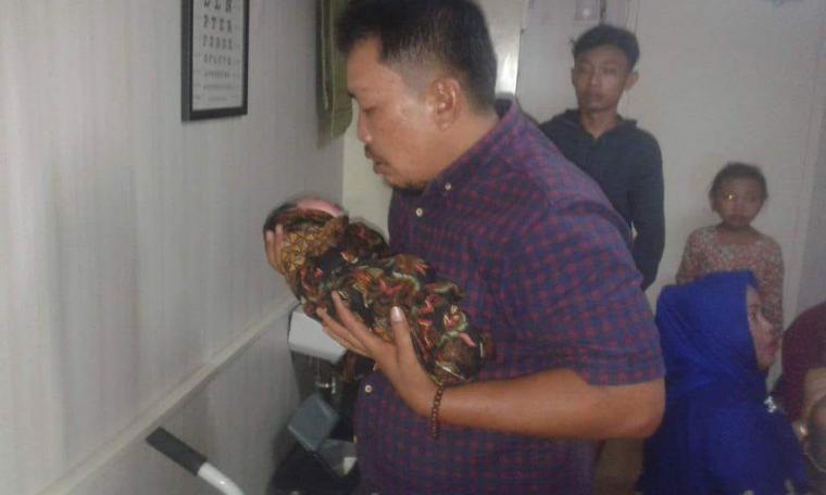 Dahlan saat menggendong sang anak yang lahir di atas KMP Kirana II. (Foto: TitikNOL)