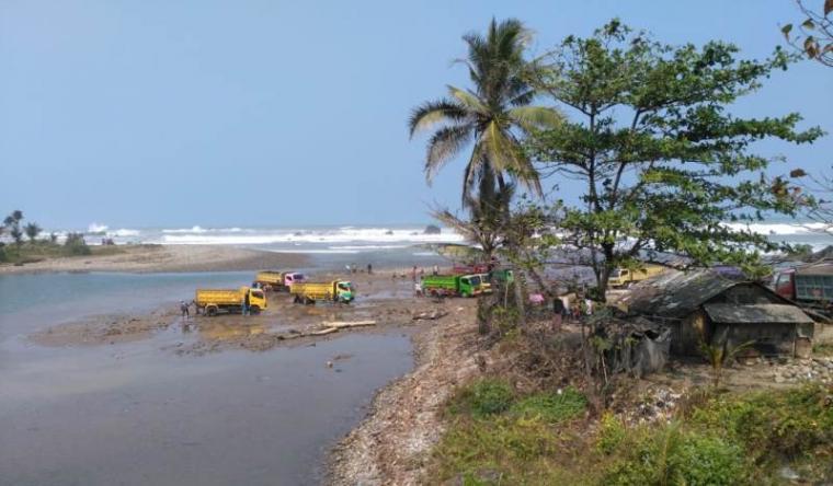 Sejumlah truk pengangkut pasir laut di pesisir Pantai Cihara tengah melakukan aktivitasnya. (Foto: TitikNOL)