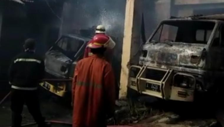 Petugas Pemadam kebakaran saat memdamkan api yang menghanguskan dua mobil. (Foto: TitikNOL)