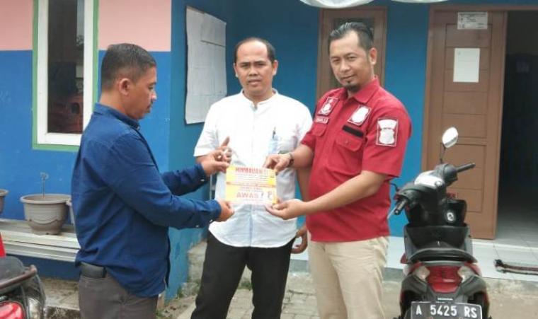 Kanit Reskrim Polsek Cipanas, Aipda Sanjoji SH (baju merah) saat memberikan pamplet himbauan kepada warga agar tidak membeli kendadaan roda dua dan empat bodong. (Foto: TitikNOL)