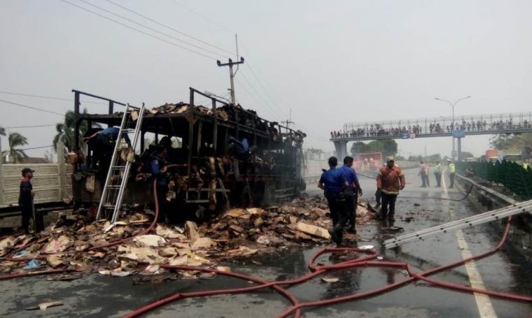 Petugas damkar saat membersihkan sisa - sisa kebakaran truk pengangkut kardus di KM 74 Tol Tangerang - Merak. (Foto: TitikNOL)