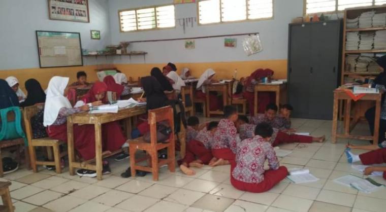 Sejumlah murid di salah satu SDN di Kecamatan Cibadak mengikuti KBM di lantai sekolah karena meja belajar di pinjam untuk Rapimnas GMNI. (Dok: TitikNOL)