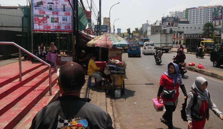 Rambu lalu lintas yang berada di depan Ramayana Ciputat, Tangsel tertutup oleh keberadaan warung semi permanen pedagang kaki lima. (Foto: TitikNOL)