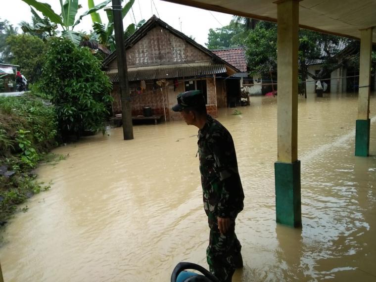 Seorang anggota TNI melintas di lokasi rumah yang terpendam banjir akibat luapan sungai. (Foto: TitikNOL)