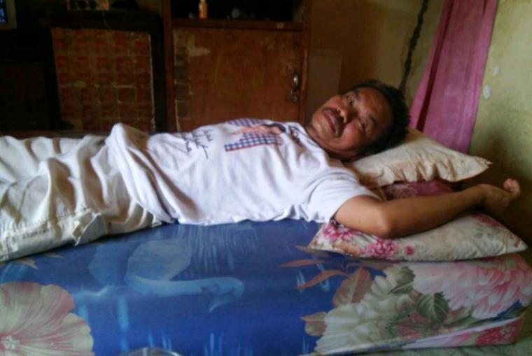 Maksum (53), salah satu eks karyawan PT Sandratex saat terbaring di tempat tidurnya melawan stroke. (Foto: TitikNOL)
