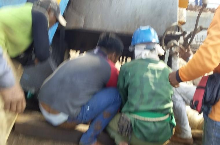 Sejumlah pekerja saat mengevakuasi badan korban yang tergencet crane. (Foto: Ist)