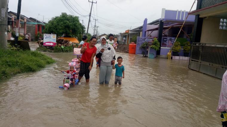 Sejumlah warga melintas di jalan perumahan yang tergenang banjir. (Foto: TitikNOL)