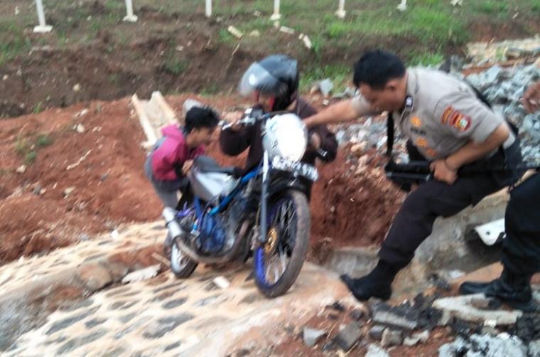 Seorang anggota polisi menarik sepeda motor milik salah seorang pembalap liar yang mencoba kabur. (Foto: TitikNOL)