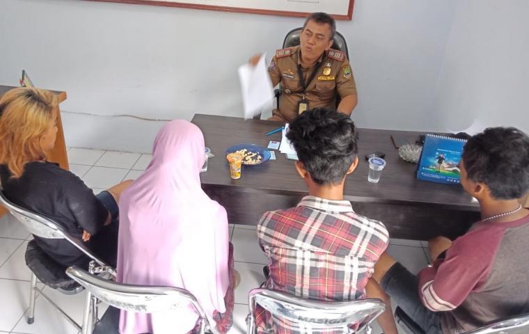 Pasangan yang diduga bukan suami - istri saat diamankan di kantor kelurahan. (Foto: TitikNOL)