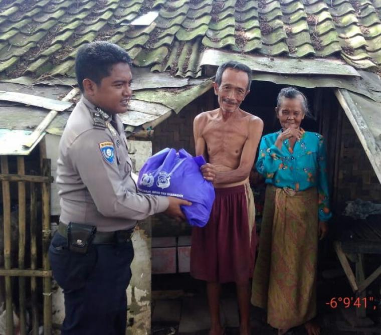 Personel kepolisian Polres Serang saat memberikan bantuan kepada warga kurang mampu. (Foto: TitikNOL)