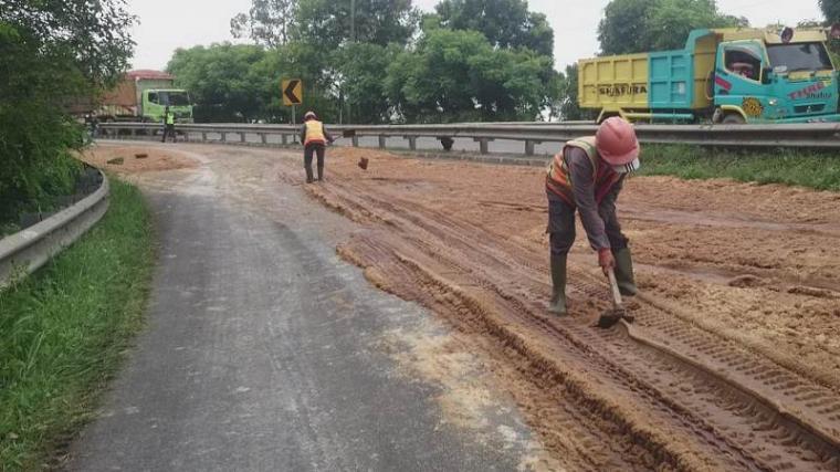 Petugas membersihkan tumpahan bahan baku gula di Tol Cilegon Timur. (Foto: TitikNOL)