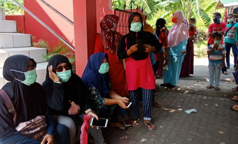 Warga menggunkan masker karena tidak kuat mencium bau kimia menyengat yang bersumber dari PT Dover Chemical. (Foto: TitikNOL)