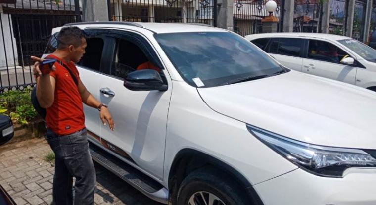 Salah seorang anggota dari Polres Cilegon mendatangi TKP pecah kaca. (Foto: TitikNOL)