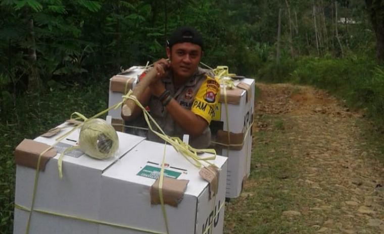 Brigadir Moch Ridwan Hermansyah mendistribusikan surat suara ke TPS 02 di Kampung Cigoler, Desa Nanggerang, Kecamatan Cirinten Kabupaten Lebak dengan cara dipikul. (Foto: TitikNOL)