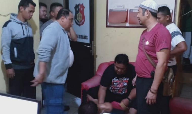 Pelaku begal (telanjang duduk dibawah) saat diamankan petugas di Mapolsek Cipanas. (Foto: TitikNOL)