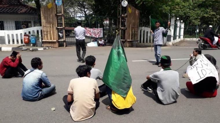 Aksi unjukrasa belasan aktivis mahasiswa dari Himpunan Mahasiswa Islam (HMI) Kabupaten Lebak di depan pintu gerbang kantor Bupati Lebak, Rabu (15/5/2019). (Foto: TitikNOL)