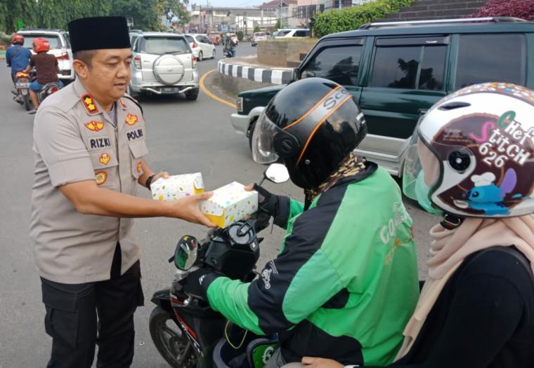 Kapolres Cilegon, AKBP Rizki Agung Prakoso saat membagikan takjil kepada pengendara sepeda motor. (Foto: TitikNOL)