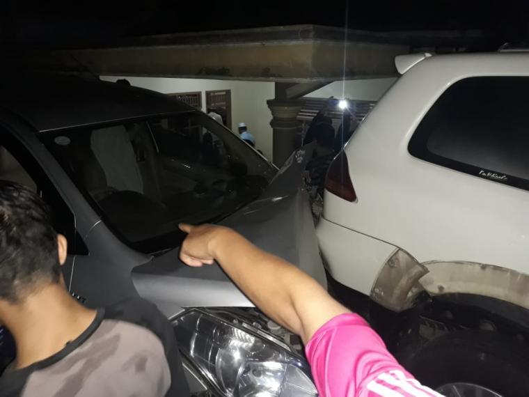 Warga menunjukan mobil Ertiga yang menabrak bagian belakang mobil Fortuner yang terparkir di jalan. (Foto: TitikNOL)