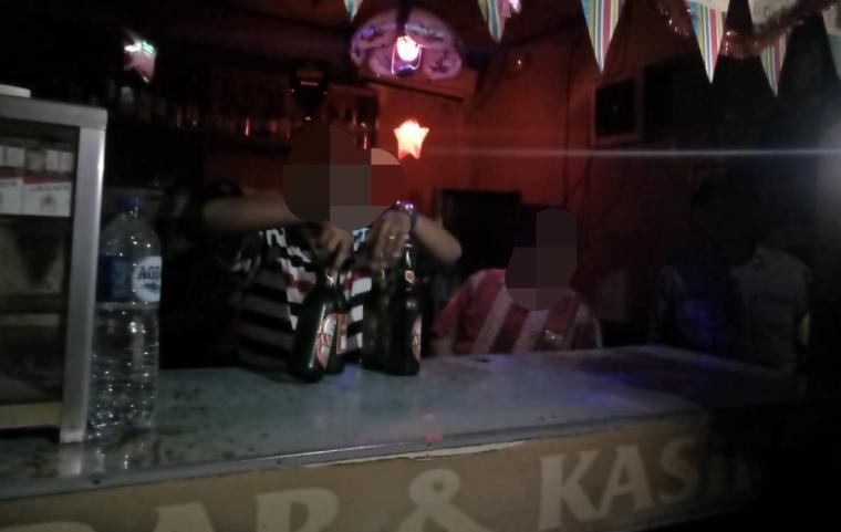 Seorang pedagang menyerahkan minuman keras, saat didatangi petugas kepolisian. (Foto: TitikNOL)