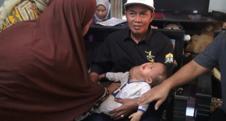 Wali kota Serang Syafrudin, saat menggendong bayi Alif yang menderita tumor ganas. (Foto: TitikNOL)