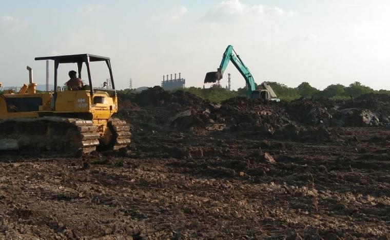 Alat berat terlihat meratakan lumpur dari proyek PT LCI di lahan Pelabuhan Warnasari. (Foto: TitikNOL)