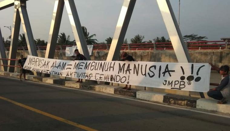 Spanduk aksi protes sejumlah warga di Kecamatan Bayah yang tergabung dalam Jaringan Masyarakat Peduli Bayah kepada PT Cemindo Gemilang. (Foto: TitikNOL)