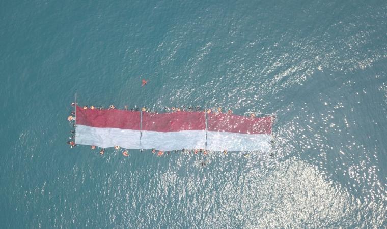 Bendera merah putih terbentang di Laut Pulau Sangiang. (Foto: Ist)