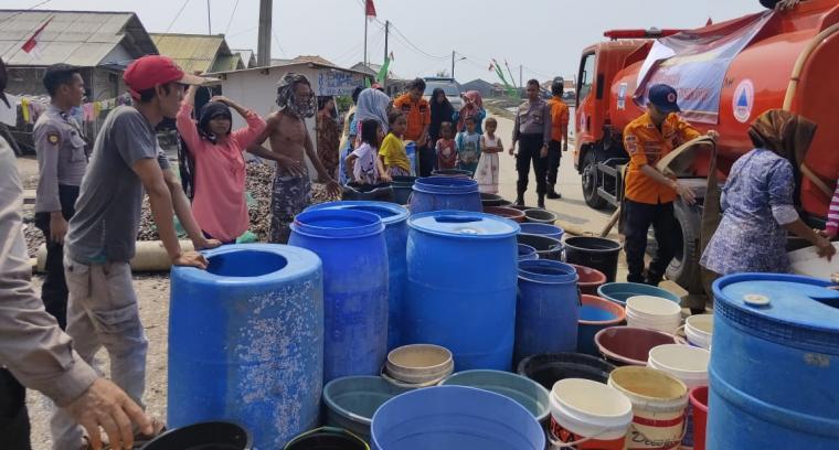 Warga mengantri dengan tertib saat personil Satuan Samapta membagikan air bersih. (Foto: TitikNOL)