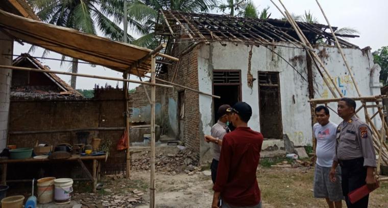 Kapolsek Cikeusal AKP Muljanto saat menyalurkan dana bantuan perbaikan rumah kepada Jaenal Abidin. (Foto: TitikNOL)