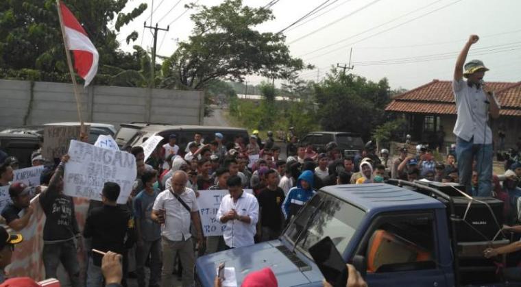 Aksi unjukrasa Ratusan warga Desa Cibuah, Kecamatan Warunggunung, Kabupaten Lebak di depan pintu gerbang gudang Indomarco. (Foto: TitikNOL)