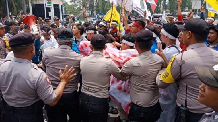 Mahasiswa saling dorong dengan polisi saat menggelaf unjuk rasa di Tugu Landmark Cilegon. (Foto: TitikNOL)