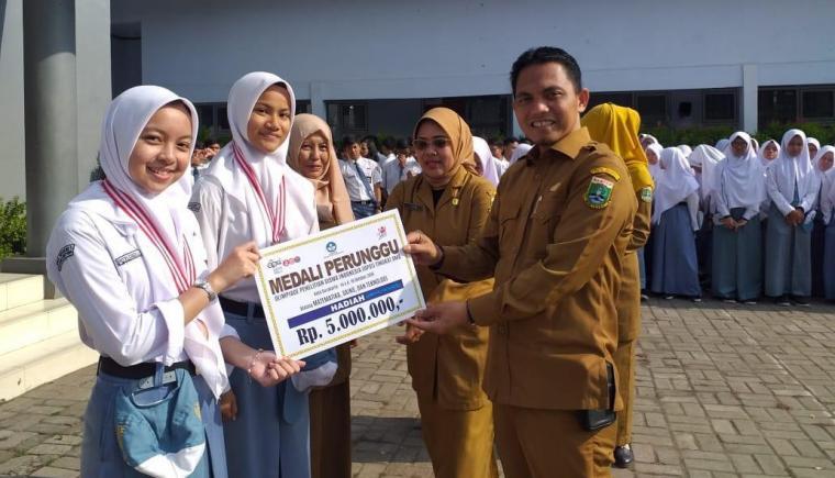 Kepala KCD Lebak Sirojudin, berfoto dengan dua siswi SMA Negeri 1 Rangkasbitung yang mendapatkan medali. (Foto: Ist)