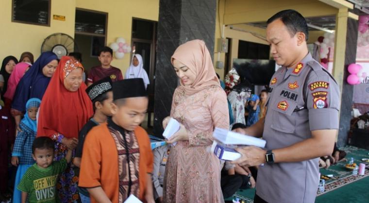 Kapolres Serang AKBP Indra Gunawan bersama isteri Widya Indra Gunawan saat memberikan santunan kepada anak yatim di Rumah Dinas Kapolres. (Foto: TitikNOL)