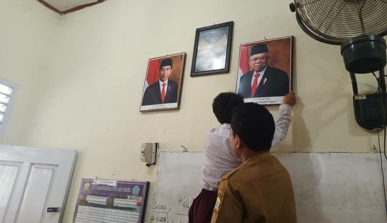 Siswa SD Negeri Serang 4, Benggala, Kota Serang saat memasang foto Presiden Joko Widodo dan Wakil Presiden KH Maruf Amin. (Foto: TitikNOL)