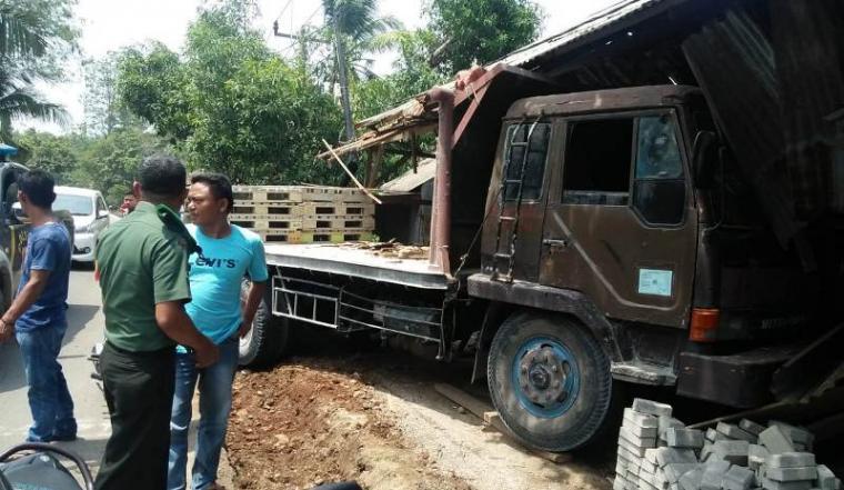 Truk trailer yang menabrak sebuah bangunan toko material di ruas jalan Warunggunung - Petir. (Foto: TitikNOL)
