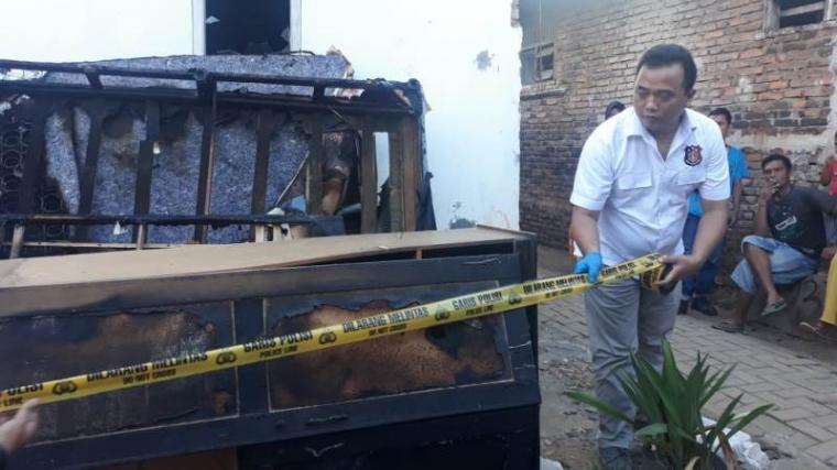 Pemasangan garis polisi di lokasi kejadian terbakarnya pasutri di dalam kamar. (Foto: TitikNOL)