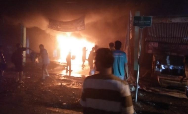 Sejumlah warga saat berusaha memadamkan api yang membakar ruko onderdil dan tabung gas elpiji milik Haji Alin yang berlokasi di Kampung Simpang RT 01 / RW 01, Desa Cilangkahan, Kecamatan Malingping. (Foto: TitikNOL)