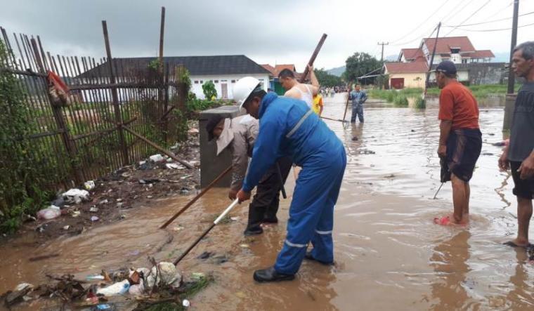 Warga membersihkan sampah supaya air banjir di Bojonegara mengalir dengan lancar ke laut. (Foto: TitikNOL)
