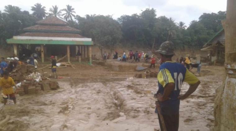 Sejumlah warga korban banjir Bandang di Kecamatan Sajira saat membersihkan tanah lumpur akibat banjir. (Foto: TitikNOL)