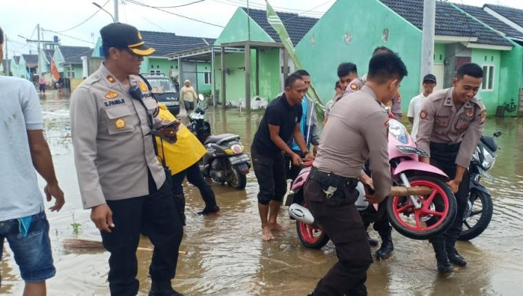Tim Satgas Bencana Alam Kepolisian Resor Serang Kabupaten, melakukan evakuasi dan penyelamatan korban yang terdampak bencana banjir di Perumahan Bumi Ketos Regency, Desa Ketos, Kecamatan Kibin Kabupaten Serang. (Foto: TitikNOL)