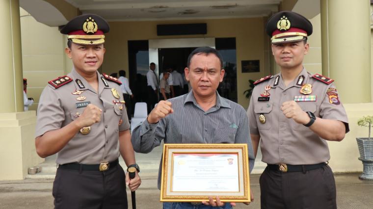 Kepala Kepolisian Resor (Kapolres) Serang, AKBP Indra Gunawan, saat memberikan penghargaan kepada Rahmat Haryono, wartawan Harian Pos Kota. (Foto: TitikNOL)