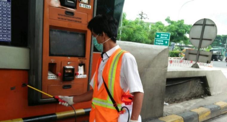 Petugas melakukan penyemprotan disinfektan di gardu E-toll. (Foto: TitikNOL)