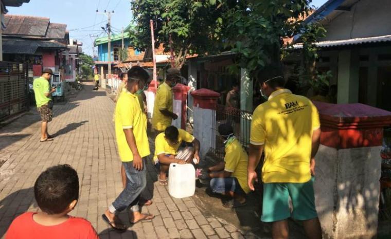 Relawan RAM melakukan penyemprotan disinfektan dipemukiman warga di Pulomerak. (Foto: TitikNOL)