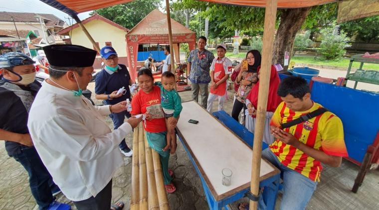 Wakil Ketua DPRD Kota Cilegon , Sokhidin dan anggota DPRD Kota Cilegon , Rahmatullah saat membagikan hand sanitizer dan masker kepada masyarakat. (Foto: TitikNOL)