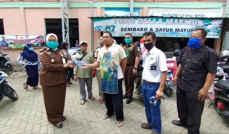 Kepala Kejari Cilegon , Andi Mirnawaty saat memberikan masker kepada salah satu pedagang di Pasar Tradisional Blok F. (Foto: TitikNOL)