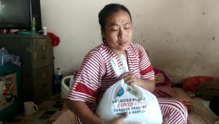 Yuli, salah satu warga Kelurahan Lontarbaru, Kecamatan Serang, Kota Serang saat menerima bantuan sembako dari Kwarda Banten dan wartawan Banten di kediamannya. (Foto: TitikNOL)