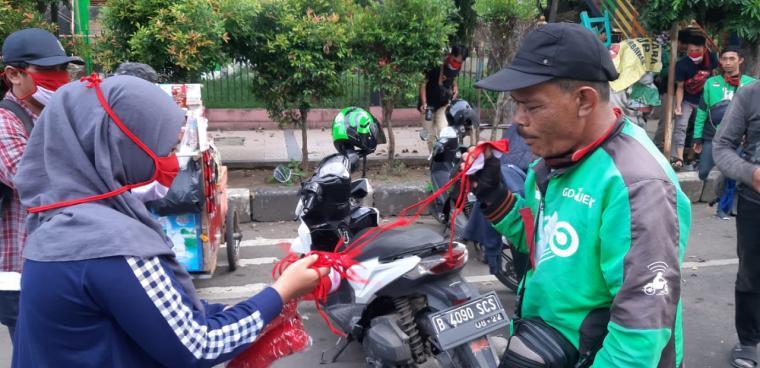 Jurnalis yang tergabung dalam Pokja Wartawan Kota Serang (PWKS) bersama para pemuda yang tergabung dalam Banten Kreatif fest, membagikan masker merah putih ke masyarakat Kota Serang, Kamis (16/4/2020). (Foto: TitikNOL)
